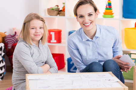 Female special educator and child patient during therapy using pictures Stock Photo