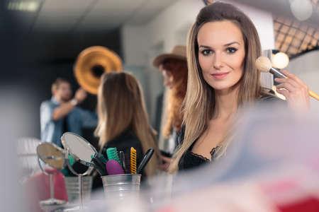 Modelo atractivo con maquillaje cepillo antes de la sesión de fotos