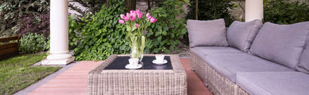 Coffee table and comfortable sofa in the garden Stock Photo