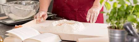 Grandmother preparing delicious flour dish in a cozy kitchen