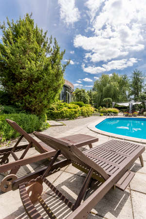 Two wooden sun loungers standing beside swiming pool Stock Photo