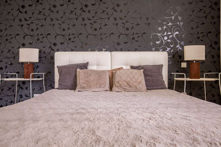 nightstands: Dark bedroom with double bed, black pattern wallpaper, two nightstands and two small lamps Stock Photo