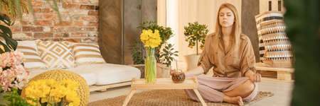Young woman sitting on the floor at home and meditating Standard-Bild