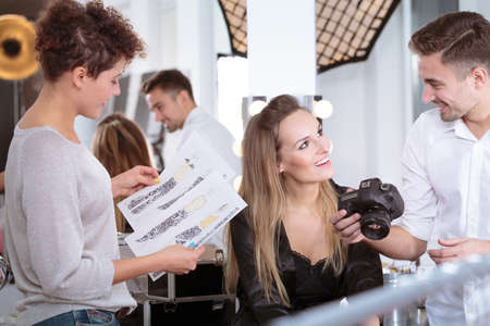 무대 뒤에서 패션 사진 작가와 이야기하는 전문 모델