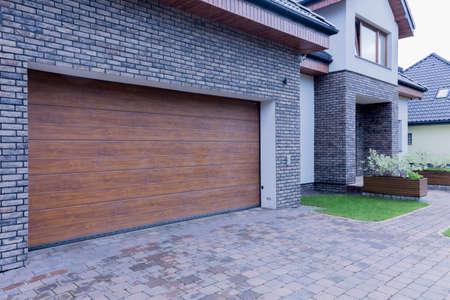 Mening van houten garagedeur en hoofdingang van losgemaakt huis Stockfoto