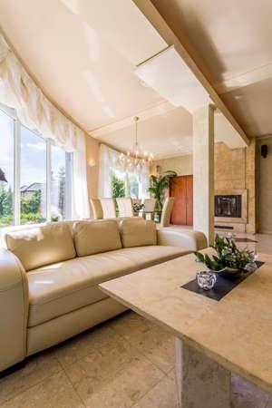 大きな窓、ベージュ革ソファとトラバーチン コーヒー テーブルの広々 としたヴィラのインテリアのイメージ