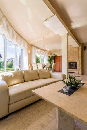 Image of a spacious villa interior with big windows, beige leather sofa and travertine coffee table Banco de Imagens