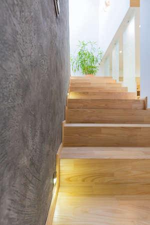 Verlichte houten trap en betonnen muur