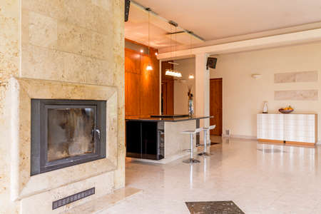 Light and spacious living room with travertine fireplace and open kitchen Standard-Bild
