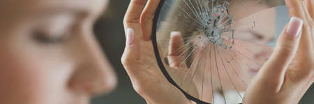 Young woman closing her eyes and holding a small broken mirror Stock Photo
