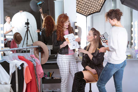 Make-up artists preparing pretty professional model for beauty shoot