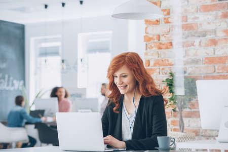 Belle femme d'affaires avec un casque souriant travaillant sur ordinateur portable dans un studio de coworking
