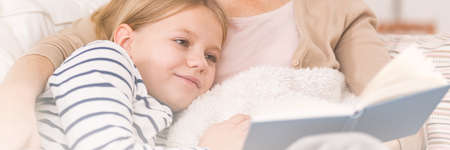 Girl reading a book with her mother Stock Photo