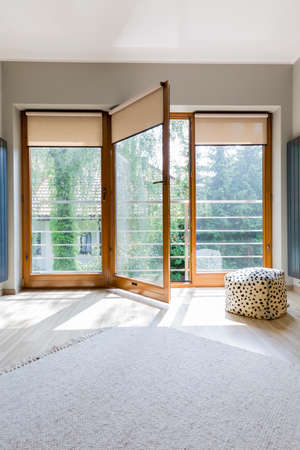 Cozy room with open window, rug and pouf 版權商用圖片
