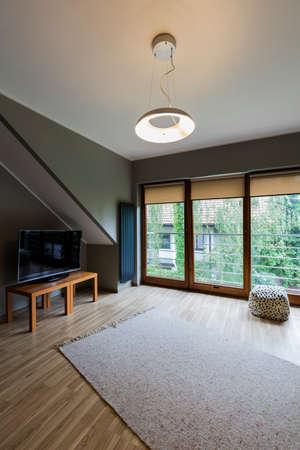 テレビ、木製の床と屋根裏部屋で居心地の良い個室 写真素材 - 86102815