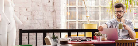 Trabajador independiente guapo en el café industrial moderno Foto de archivo - 80781250