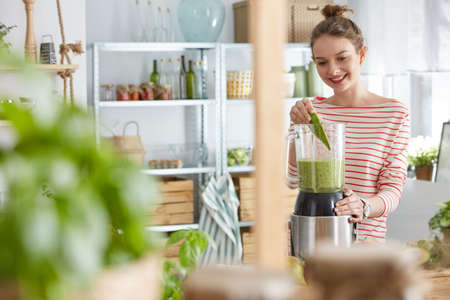 Happy young woman using blender to prepare a smoothie Stock Photo