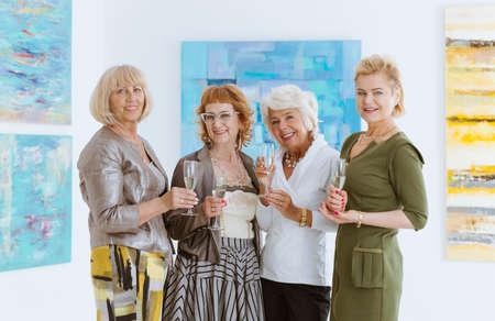 Four senior girlfriends on meeting in art gallery