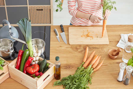 Wooden table with box of vegetables and spices in modern kitchen Stok Fotoğraf