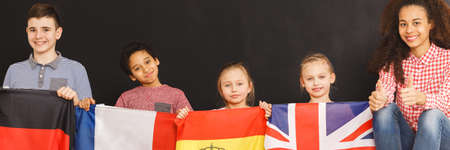 Young teacher and kids with flags in language school Stock Photo