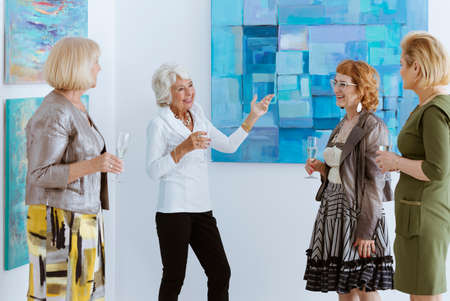 curator: Active senior women on painting opening in museum