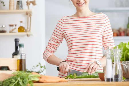 Glimlachende vrouw die een salade in haar keuken voorbereidt