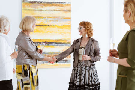 curator: Senior woman shaking hands with curator of exhibition in gallery