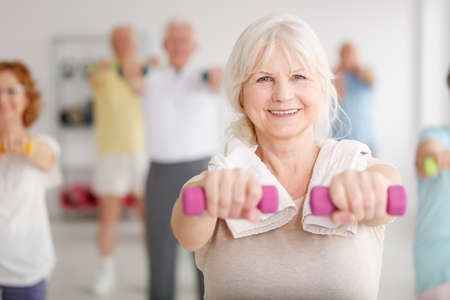 Senior woman exercising with pink dumbbells during classes Stockfoto