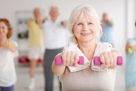 Ltere Frau, die mit rosa Dummköpfen während der Klassen trainiert Standard-Bild - 81369113