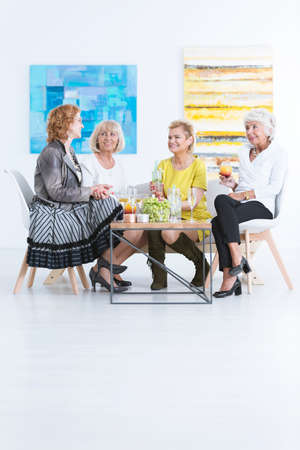 curator: Group of senior friends having drinks and snacks in art gallery Stock Photo