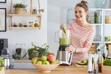 Happy woman preparing healthy green smoothie in her kitchen Banco de Imagens