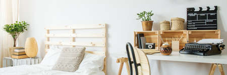 White bedroom with wooden bed, desk and chair, panorama