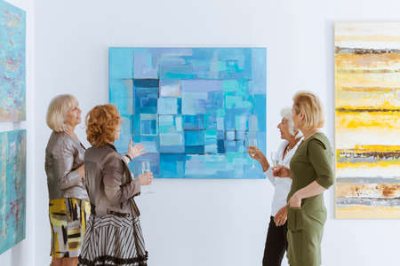Four elegant friends looking at painting in museum