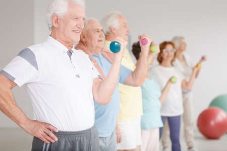 Group of active seniors using dumbbells during sport classes