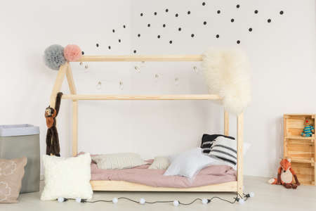 Scandi design of baby room with wooden bed and soft accessories