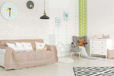 レンガの壁と緑のサボテンの壁紙と居心地の良い赤ちゃんの部屋
