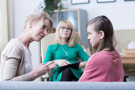 Worried mother talking to troubled teenage girl during psychological visit Reklamní fotografie