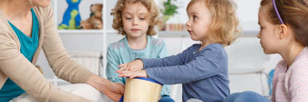 Little kids sitting in circle with a drum Фото со стока