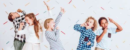 pretending: Happy kids pretending to sing at the school party Stock Photo