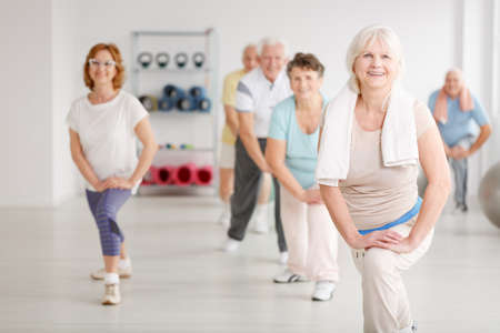 Elderly people exercising in a group in fitness club Stock Photo