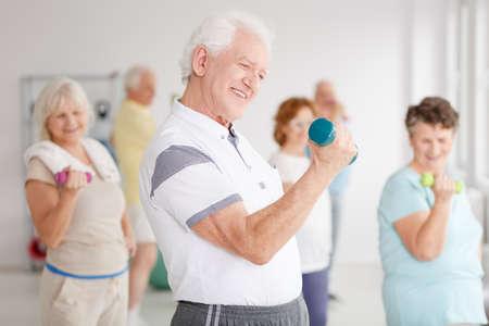 Older man exercising biceps using dumbbell during fitness classes