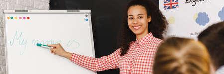 Jonge mooie engels leraar tijdens de lessen met studenten