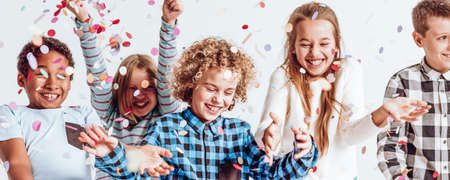 Glimlachende kinderen spelen met confetti op de verjaardagspartij