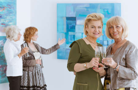 Four elegant women on opening in art gallery drinking champagne