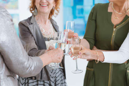 curator: Close-up of happy women drinking champagne in glasses