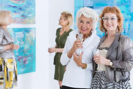 Happy older friends  spending afternoon in art gallery