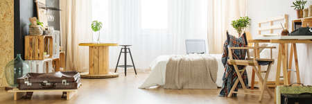 Beige, modern bedroom with bed, desk, chair and crate furniture Stock Photo
