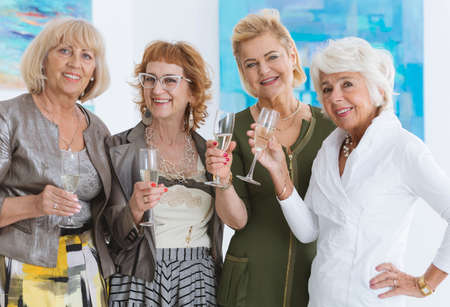 Elegant senior girlfriends drinking champagne in museum
