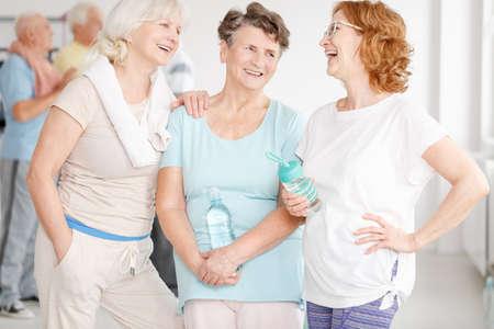 Gelukkige bejaarde actieve vriendinnen die in een sportschool roddelen