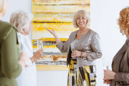 Happy elderly woman presenting the painting in art gallery Stock Photo
